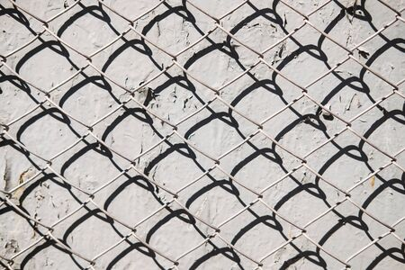 Metal mesh pattern on concrete wall background with shadow. Abstract texture