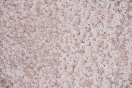 The surface of a pink salt lake covered with salt at sunset. Lovely soft pink texture. Close Up.