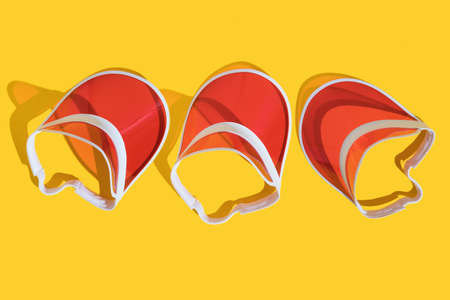 Bright red sports sun cap on a yellow background with a hard shadow. Creative texture food banner. Top view. Flat lay.