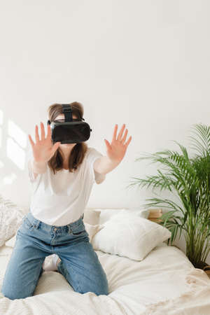 Young beautiful woman in white t-shirt and blue jeans plays game, dances with virtual reality headset in bed. Concept of entertainment, learning at home during quarantine.