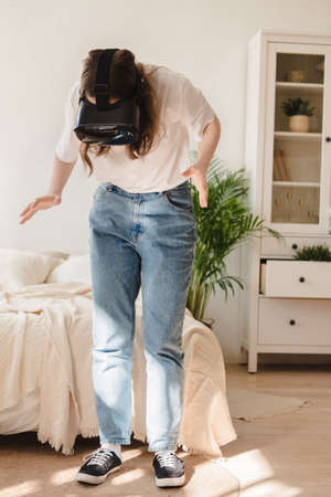 Young woman in jeans and white T-shirt wearing virtual reality helmet plays game, works, watches video in room next to bed. Concept of modern technology, VR, augmented virtual games, entertainment.