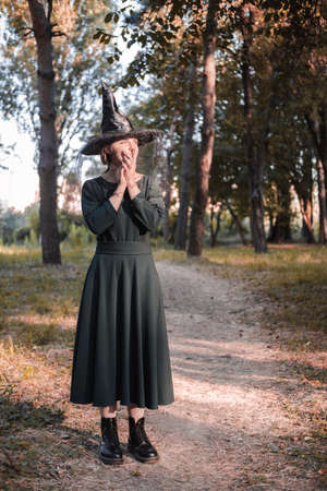 Pretty young beautiful woman in dark dress and witch hat standing in middle of autumn woods or park. Halloween party costume. Portrait in full growth. Shadow on the face. 免版税图像