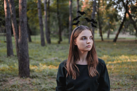Young cute beautiful woman in dark dress and headband with bats on her head. Halloween party costume. Forest, park with autumn trees. 免版税图像