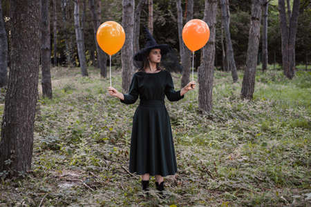 Young cute beautiful woman in dark dress and witchs hat holds orange balloons in her hands. Halloween party costume. Forest, park with autumn trees. 免版税图像
