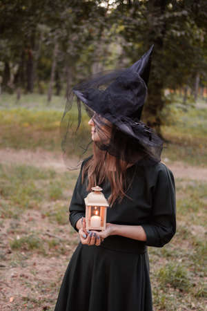 Young woman in dark dress and witchs hat holds lantern with candles in her hands and illuminates the forest. Halloween party costume. Park with autumn trees. Фото со стока