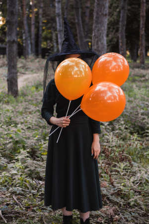 Young cute beautiful woman in dark dress and witchs hat holds orange balloons in her hands. Halloween party costume. Forest, park with autumn trees. Stock fotó
