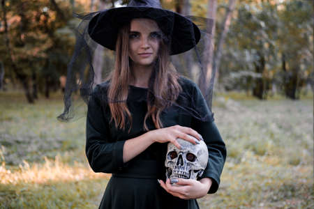 Young beautiful cute woman in dark dress and witchs hat holds a skull in her hands. Halloween party costume. Forest, park with autumn trees.