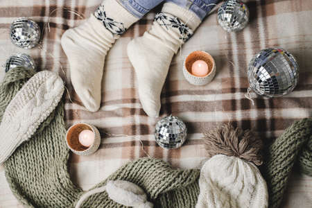 Young woman is sitting on the bed in cozy knitted woolen white sweater, socks and holding toy disco ball in her hands.
