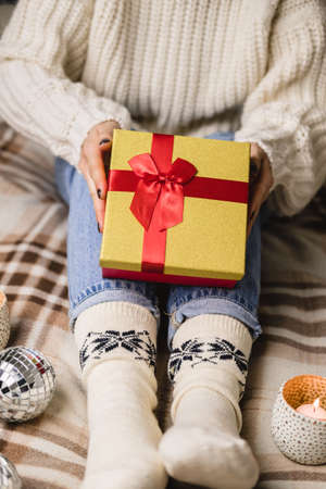 Young woman sits on bed in cozy knitted wool white sweater and holding gift-box with red gold.