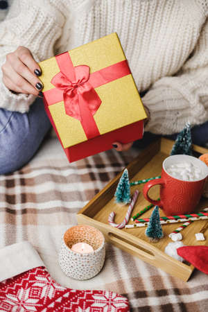 Young woman sits on bed in cozy knitted wool white sweater and holding gift-box with red gold. Reklamní fotografie - 157232057
