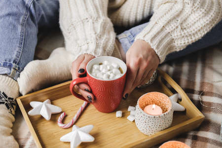 Young woman sits on plaid in cozy knitted woolen sweater and holds cup of cocoa with marshmallows