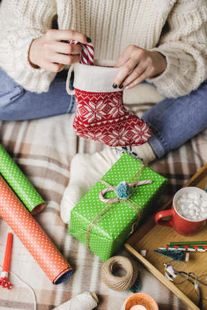 Young woman sits on plaid in cozy knitted woolen sweater and puts striped lollipop cane in Christmas sock for gifts.
