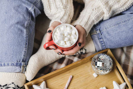 Young woman sits on plaid in cozy knitted woolen white sweater and holds cup of cocoa with marshmallows.