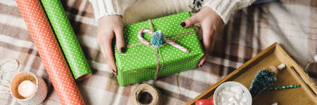 Young woman sits on plaid in cozy knitted woolen white sweater, socks and wraps Christmas gift in polka dot wrapping paper.