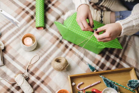 Young woman sits on plaid in cozy knitted woolen white sweater, socks and wraps Christmas gift in polka dot wrapping paper. Reklamní fotografie - 157232024