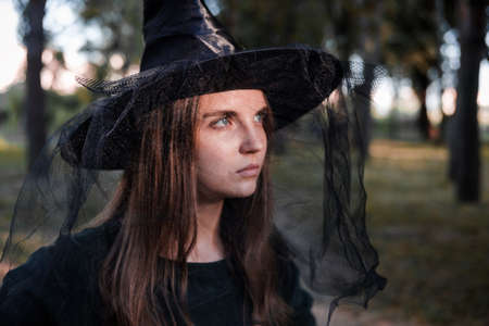Pretty young beautiful woman in dark dress and witch hat standing in the middle of the autumn woods or park. Halloween party costume. Close-up portrait. Shadow on her face.