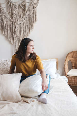 Young beautiful girl student in an orange T-shirt and blue jeans sits on bed with pillows and listens to an audiobook, music, podcast on headphones. Self-education concept at home during quarantine. Reklamní fotografie