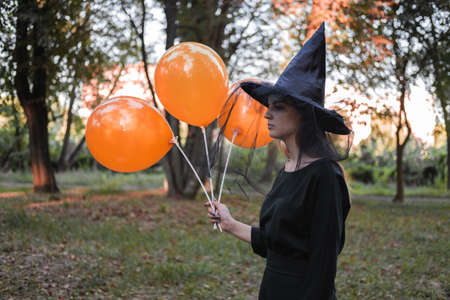 Young cute beautiful woman in dark dress and witchs hat holds orange balloons in her hands. Halloween party costume. Forest, park with autumn trees. Reklamní fotografie - 157150493