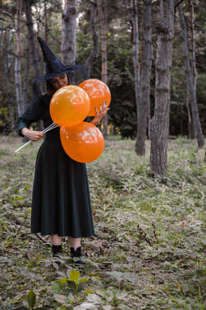Young cute beautiful woman in dark dress and witchs hat holds orange balloons in her hands. Halloween party costume. Forest, park with autumn trees. Reklamní fotografie - 157150174
