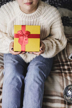 Young woman sits on bed in cozy knitted wool white sweater and holding gift-box with red gold. Hygge, New Years, Christmas, holiday preparations. Candles, Christmas balls, gifts, cocoa marshmallows. Reklamní fotografie - 157150897