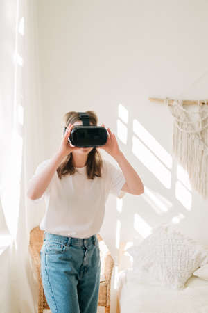 Young beautiful woman in white t-shirt and blue jeans plays game, dances with virtual reality headset helmet by the window in her room. Concept of entertainment, learning at home during quarantine