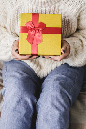 Young woman sits on bed in cozy knitted wool white sweater and holding gift-box with red gold. Hygge, New Years, Christmas, holiday preparations. Candles, Christmas balls, gifts, cocoa marshmallows Reklamní fotografie - 159019722