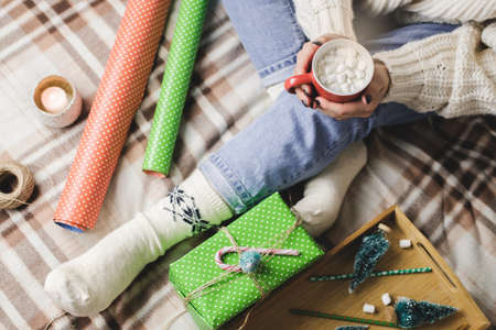 Young woman sits on plaid in cozy knitted woolen white sweater and holds cup of cocoa with marshmallows. Hygge New Year, preparation for holidays. Candles, Christmas balls, gifts, wrapping paper Reklamní fotografie - 159019753