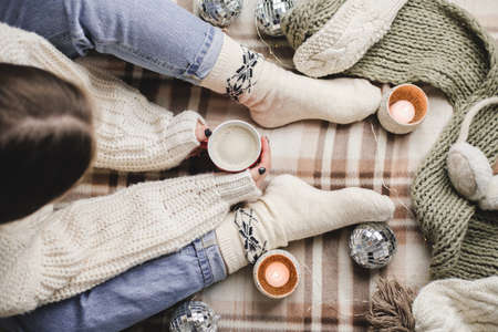 Young woman sits on plaid in cozy knitted woolen white sweater and socks holds cup of cocoa in her hands. Hygge New Year, cozy Christmas, preparation for holidays. Candles, Christmas balls Reklamní fotografie - 159019754