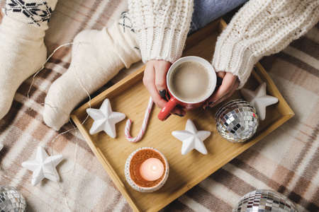 Young woman sits on plaid in hugge cozy knitted woolen white sweater and holds cup of cocoa in her hands. Wooden tray with mug of chocolate with toy tree, candle, stars Reklamní fotografie - 159019758