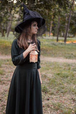 Young woman in dark dress and witchs hat holds lantern with candles in her hands and illuminates the forest. Halloween party costume. Park with autumn trees. 写真素材