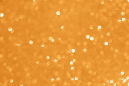 Abstract glitter blurred shiny marigold orange background. Bright sparkling bokeh wallpaper style. Festive Christmas holiday futuristic texture