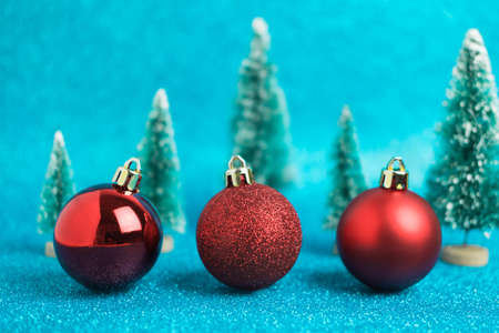 Christmas festive background with three red christmas balls, toy trees. Abstract glitter blurred background shiny blue ai aqua. Bright sparkling wallpaper with bokeh texture Reklamní fotografie - 159019994