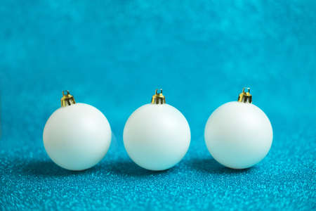 Christmas festive background with three white christmas balls. Abstract glitter blurred background shiny blue ai aqua. Bright sparkling wallpaper with bokeh texture
