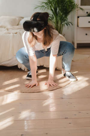 Young woman in jeans and white T-shirt wearing virtual reality helmet plays game, works, watches video in room next to bed. Concept of modern technology, VR, augmented virtual games, entertainment Reklamní fotografie - 159020026