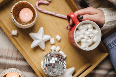 Young woman sits on plaid in cozy knitted woolen sweater and holds cup of cocoa with marshmallows. Hygge New Year, cozy Christmas, preparation for holidays. Wooden tray with candles, stars, balls.