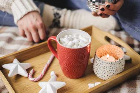 Young woman sits on plaid in cozy knitted woolen white sweater and holds cup of cocoa with marshmallows. Hygge banner New Year, cozy preparation for holidays. Candles, Christmas balls in wooden tray Reklamní fotografie - 159020115