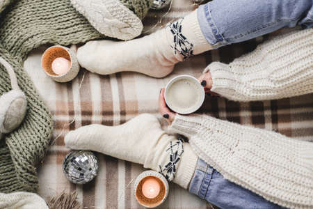 Young woman sits on plaid in cozy knitted woolen white sweater and socks holds cup of cocoa in her hands. Hygge New Year, cozy Christmas, preparation for holidays. Candles, Christmas balls Reklamní fotografie