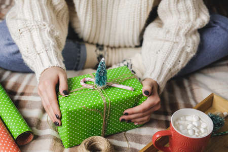 Young woman sits on plaid in cozy knitted woolen white sweater, socks and wraps Christmas gift in polka dot wrapping paper. Wooden tray with mug of cocoa with marshmallows, toy tree, candle, straws Reklamní fotografie
