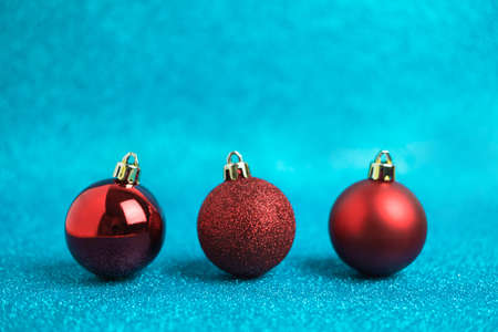 Christmas festive background with three red christmas balls. Abstract glitter blurred background shiny blue ai aqua. Bright sparkling wallpaper with bokeh texture Reklamní fotografie