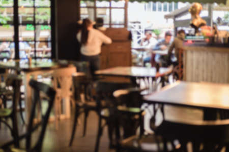 Bright defocused blurred background with unrecognizable people in a cafe. Abstract image of crowd of people in public place.