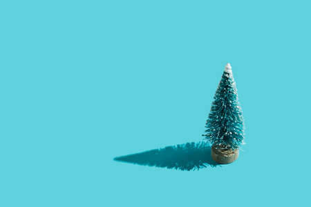 Toy plastic green Christmas tree on minimal blue background with hard shadow. Christmas and New Year background for congratulations on the coming holidays. Flat lay. Top view. Place for text.