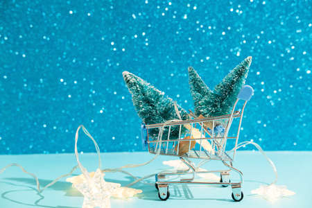 Christmas minimal festive background with star garland in supermarket basket, toy trees. Abstract Christmas and New Year color background blue ai aqua. Bright sparkling wallpaper. Reklamní fotografie