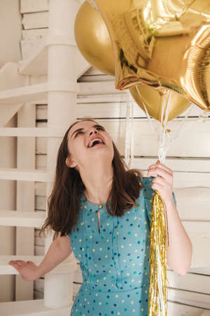 Young beautiful girl in blue dress with white polka dots celebrates her birthday and enjoys the golden balloons. Birthday alone at home during self-isolation. Reklamní fotografie - 159199268