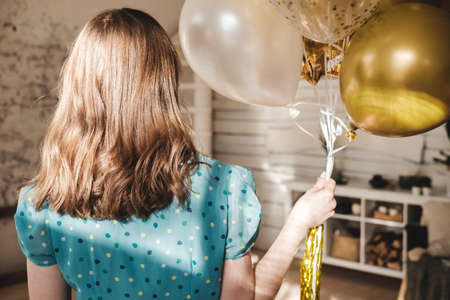 Young beautiful girl in blue dress with white polka dots celebrates her birthday and enjoys the golden balloons. Birthday alone at home during self-isolation. Reklamní fotografie - 159199355