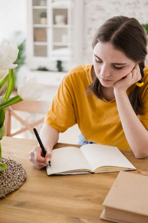 Young beautiful woman in yellow t-shirt engaged in work, online business, studying sitting at table at home. Self-isolation, study, work during quarantine, pandemic. Remote job, education, student. Reklamní fotografie - 159199923