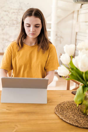 Young beautiful woman in yellow t-shirt usimg tablet for work, online business, studying sitting at home. Self-isolation, study, work during quarantine, pandemic. Remote job, education, student. Reklamní fotografie - 159199228