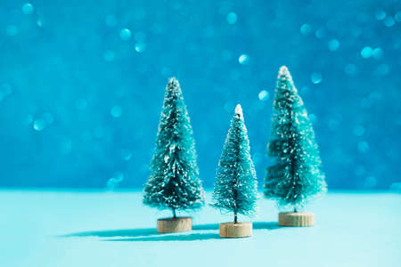 Christmas minimal festive background with christmas toy tree. Abstract glitter blurred background shiny blue ai aqua. Bright sparkling wallpaper with bokeh texture.