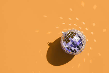 Christmas minimal festive background with christmas tree toy disco ball. Abstract glitter blurred background shiny color of the year orange marigold. Bright sparkling wallpaper with bokeh texture.