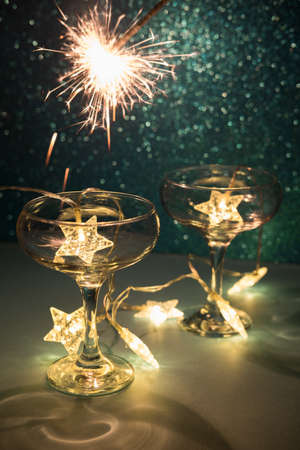 Christmas minimal festive background with star garland in glasses of champagne. Abstract Christmas and New Year color glitter blurred background shiny blue ai aqua. Bright sparkling sparklers texture. Reklamní fotografie