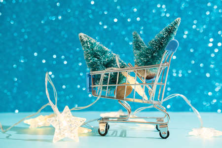 Christmas minimal festive background with star garland in supermarket basket, toy trees. Abstract Christmas and New Year color background blue ai aqua. Bright sparkling wallpaper. Reklamní fotografie - 159253037